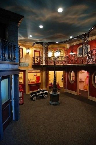 """Playroom - LOVE THIS! Even if you only did this in a one-story height basement it would be pretty darn cute. Paint the ceiling, building the little closet """"stores"""" and install mini doors and windows."""