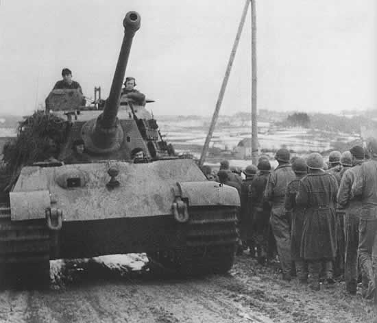 Captured U.S. soldiers march into captivity past a King Tiger tank during the Battle of the Bulge.