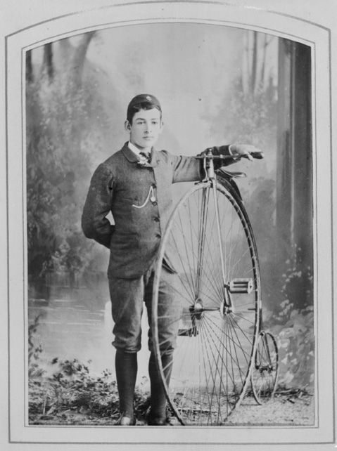 Showing Master T B Wallis wearing a suit, boots and a cap, uniform of the Waitemata Bicycle Club, standing beside a Penny Farthing bicycle
