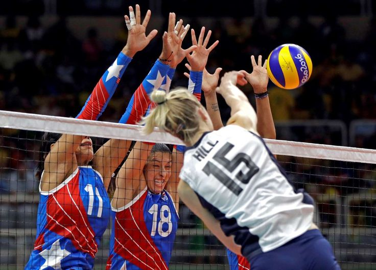 One against three:    The United States' Kim Hill spikes the ball over a trio of Puerto Rico players during a women's preliminary volleyball match