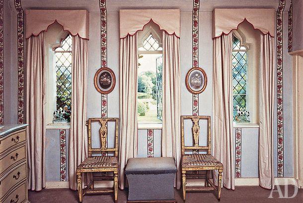 Дом в Хэмпшире. В достаточно небольшом помещении использовали приемы оформления дворцовых интерьеров: маленькие узкие окна по всем правилам украсили шторами и ламбрекенами, в простенках нарисовали декоративные бордюры с медальонами и расставили стулья. Эти детали ассоциируются с парадным стилем и зрительно меняют масштаб комнаты– она кажется просторнее и торжественнее.