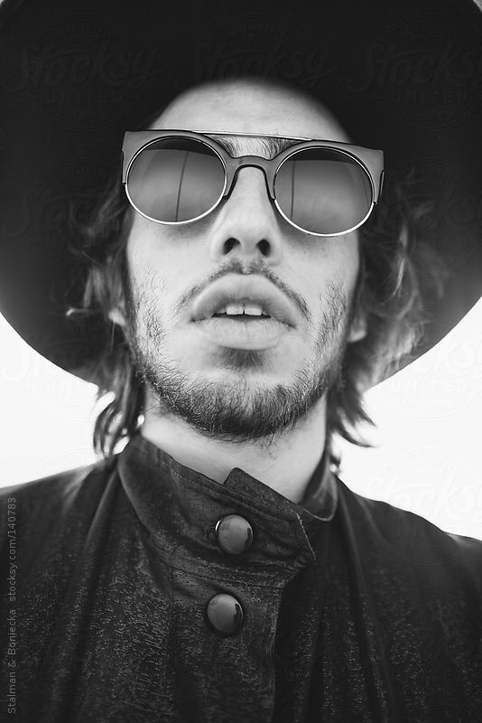 A portrait of a man wearing reflective sunglasses looking up into the sky by stalmanandboniecka | Stocksy United