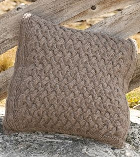 Den fine pude med snoninger er strikket i brunmeleret uld