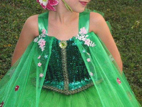 We are presenting our inspired version of the frozen fever dress worn by Elsa. She looked like springtime in this dress. Our version is made with teal sequins adorning the bodice with a sweetheart neckline and a beautiful emerald green brooch. The 6 layer skirt is made with high