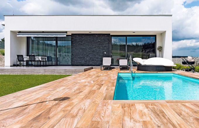 Rodinný dům ve tvaru bílé minimalistické kostky je postavený z nízkoenergetických prefabrikovaných panelů. Charakter stavby i posazení na pozemku splnil majitelce sen o středomořském bydlení