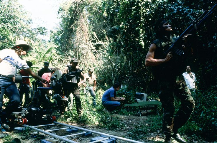 The camera follows Sonny Landham into the bush.