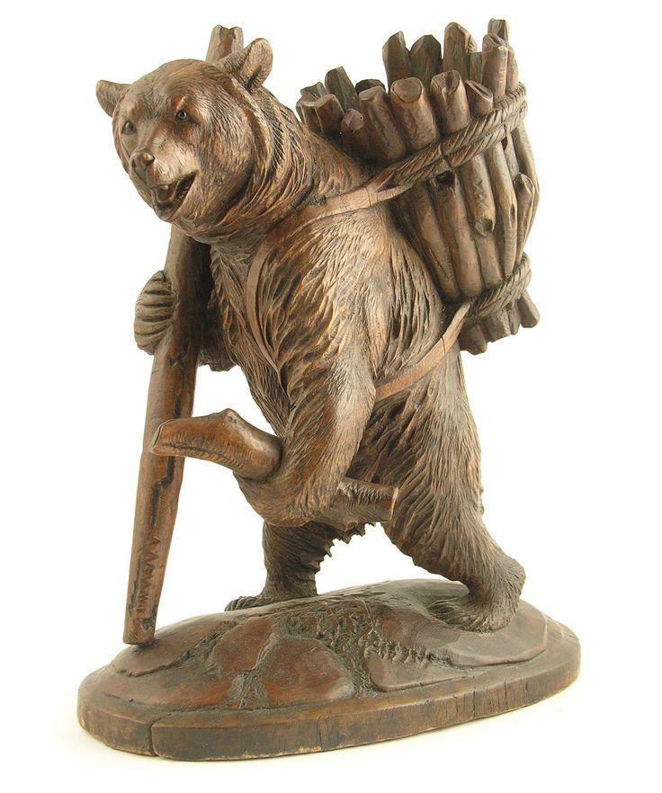 A Black Forest carved wood model of a standing bear, carrying fire wood, on a naturalistic base, late 19th / early 20th century, originally a sprit decanter holder, 11.25in (28.5cm) h, 9.25in (23.4cm) w, 5.25in (13cm) d.