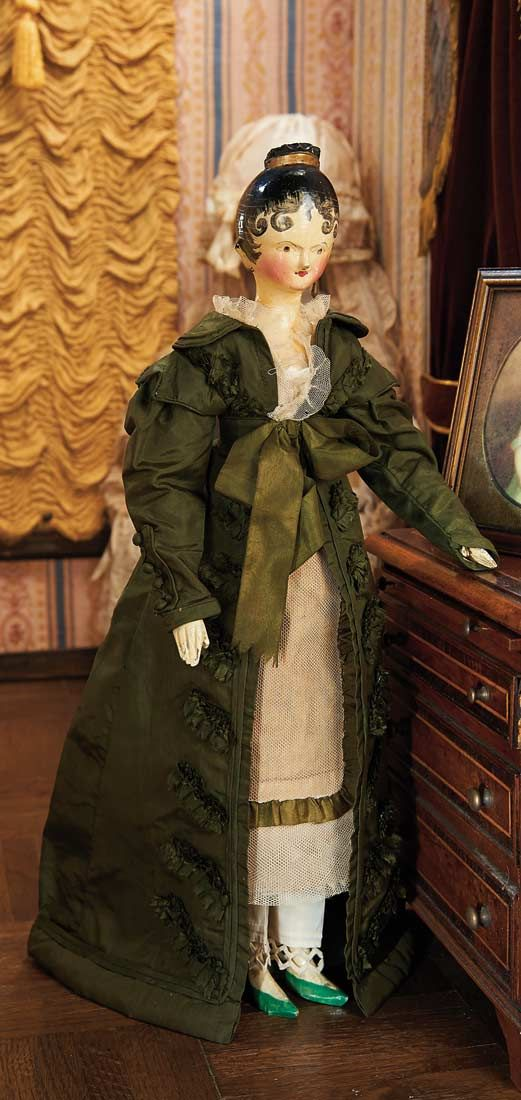 Doll, ca 1830, wearing early costume comprising tulle gown with ruffled yoke,undergarments,and padded green silk day dress with pleated ruffles.