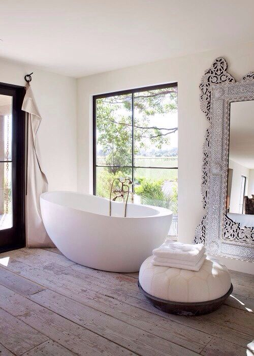 white bathroom with beautiful wooden floor and huge mirror