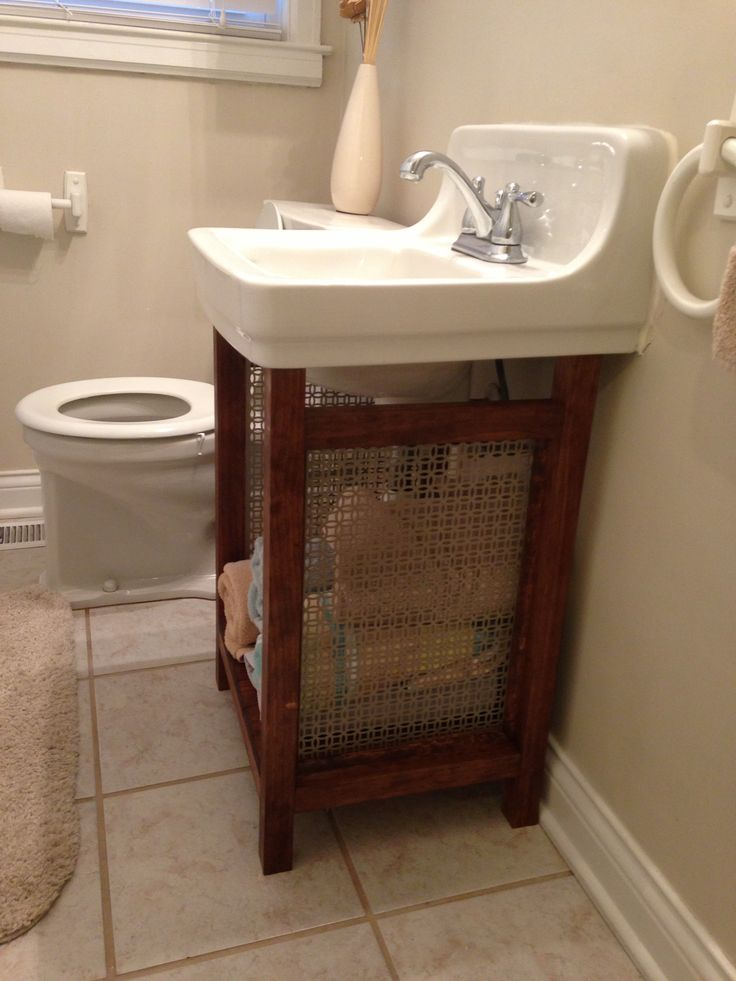 Solution for old wall mounted sink that is super hard to replace: pine boards and vent grate make a cute, open vanity with plenty of storage and hides the ugly old pipes.