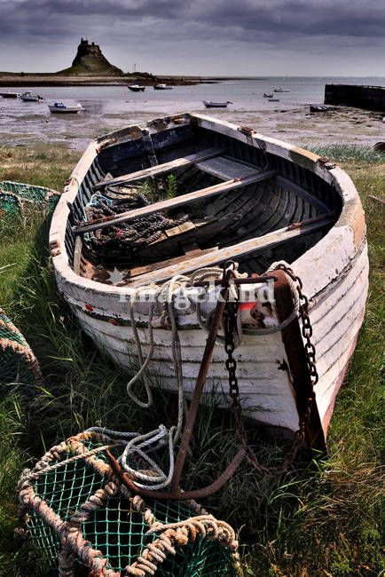 """""""Old boat and lobster pots - Lindisfarne"""" by Dave Lawrance, Cumbria // A landscape photo of an old fishing boat on Lindisfarne (Holy Island), just off the Northumberland coast, North-East England. Lindisfarne Castle features in the background. // Imagekind.com -- Buy stunning, museum-quality fine art prints, framed prints, and canvas prints directly from independent working artists and photographers."""
