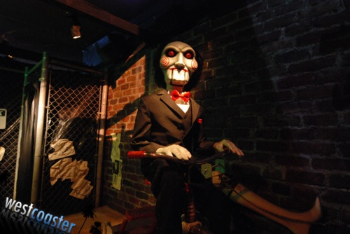 """HHN 2010, Universal Studios Hollywood Jigsaw's iconic puppet, Billy, looks down on guests in Halloween Horror Nights Hollywood's house, """"SAW: Game On."""" Photo by Albert Lam & Dan Angona, courtesy Westcoaster.net."""