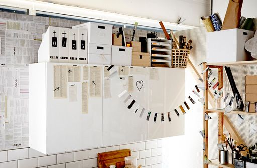 IKEA KVISSLE magazine files and TJENA boxes on top of white kitchen wall cabinets
