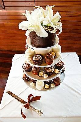 una scelta che personalmente apprezzo molto...in cima la torta da tagliare, nei piani sottostanti monoporzioni per gli invitati (qui sono cupcake ma si può optare per riproduzioni in piccolo della torta destinata al taglio). Ogni monoporzione andrebbe decorata come la torta principale.