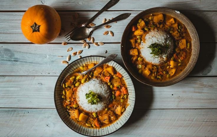 Vegan Pumpkin Katsu Curry Recipe. Two servings of curry with a whole squash next to them and some oven roasted pumpkin seeds sprinkled on the table.