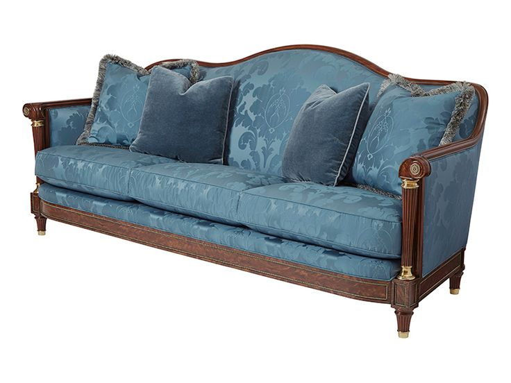 A fine mahogany sofa, the undulating tight upholstered back with scroll arm supports on turned and reeded tapering columns with brass capitals and bases, the loose bench cushion seat with four throw pillows, the flame veneered panelled seatrail with beaded brass moulding, on tapering legs with brass cappings.
