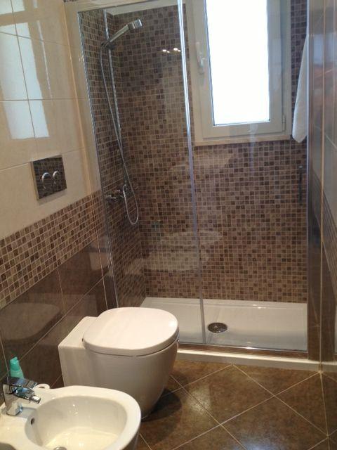 Bagno con doccia in mosaico sotto finestra.