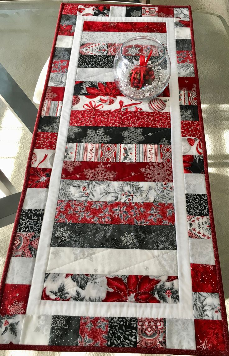 Its not too late! This beautiful quilted Christmas table runner measures 37 3/4 x 16 1/4 and is made from 100% cotton fabric. The top of the table runner is made with Robert Kaufman Holiday Flourish fabric in Christmas colors of red, black, gray, white and metallic silver. The