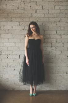 Black tulle strapless tea-length cocktail dress. Strapless bodice with subtle curved neckline, pencil skirt with layered tulle.