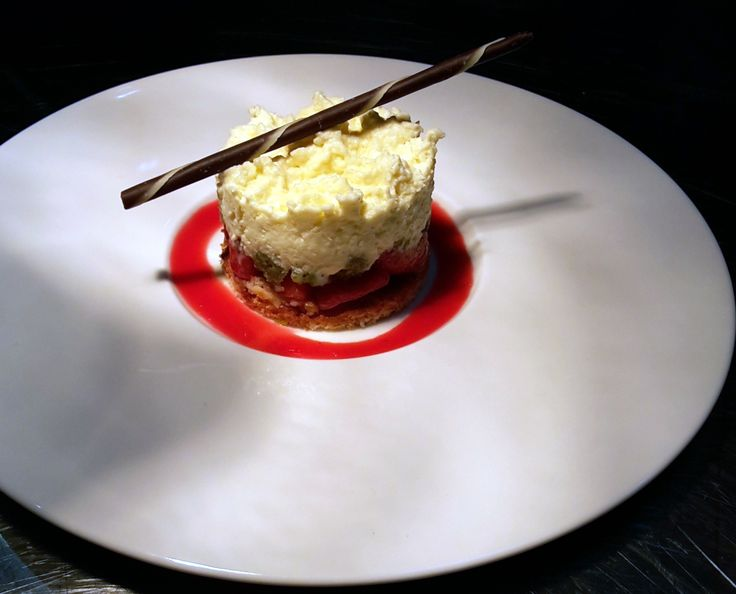 Cake with caramelized strawberry and pistachio confit with honey on a white chocolate mousse