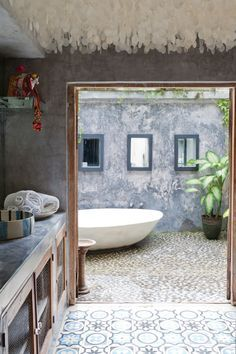 Bathroom An outdoor bath takes advantage of the tropical weather. The patina of the wall contrasts beautifully with the..(Modern tropical house on Bali Island, Indonesia )