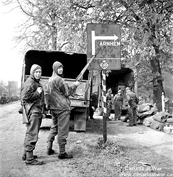Note the supplies! Private George Pope and Private Dennis Townsend point with rifles at road sign showing Arnhem. (http://www.canadaatwar.ca/photo/14/the-netherlands/)