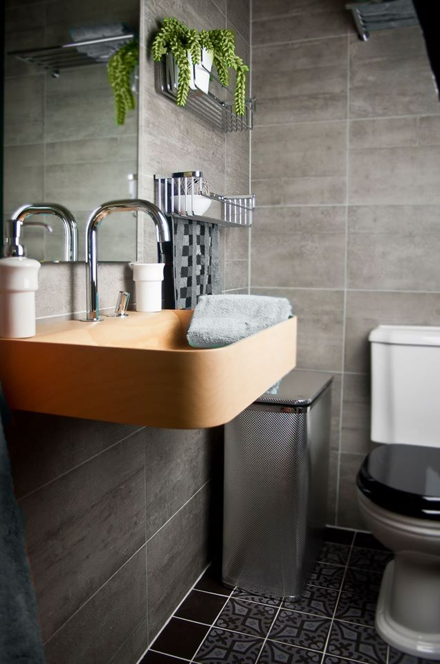 Bathroom in grey and black, with wood basin.