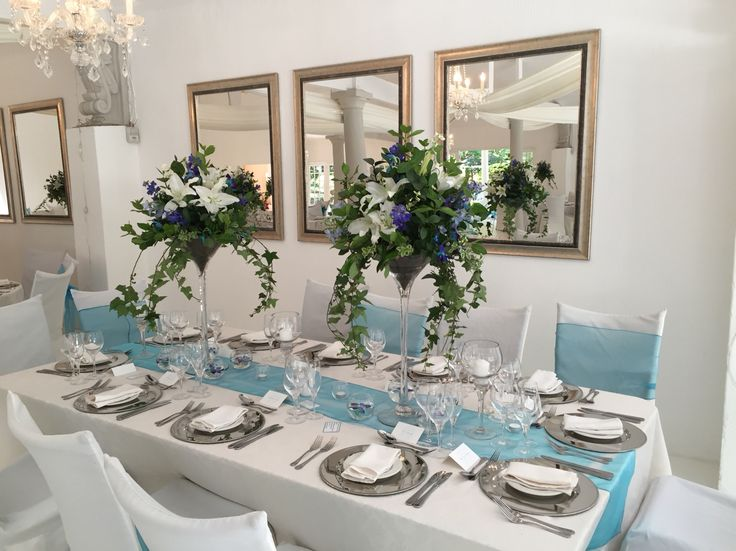 Tall blue and white centerpieces with dendrobium orchids and Casablanca lilies. Designed by Bliss Floral Creations
