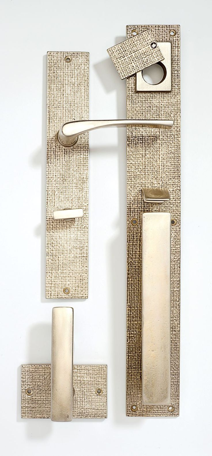 Smooth handles and locks are combined with strikingly textured plates in the Burlap hardware collection by Sun Valley Bronze. Clockwise from top left are the patio set ($781), the mortise-lock front-entry set ($1,552), and the tubular passage set ($512), all in white bronze. Ten finishes are offered. sunvalleybronze.com