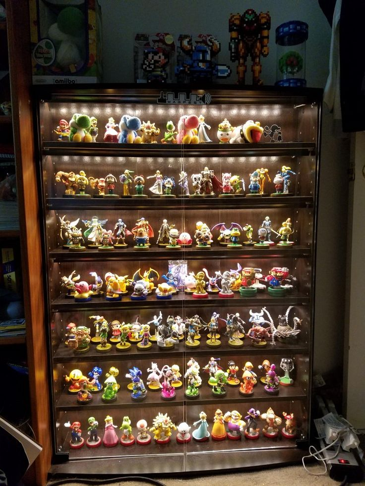 Photo credit r/amiibo u/AirDancerExtreme Modified from Amazon. The base shelf is a Sauder Multimedia Storage Tower. The LEDs are from Ikea. The glass doors and wainscotting were made and installed by a local custome cabinet designer. https://www.amazon.com/Sauder-Multimedia-Storage-Cinnamon-Cherry/dp/B002RRH23W