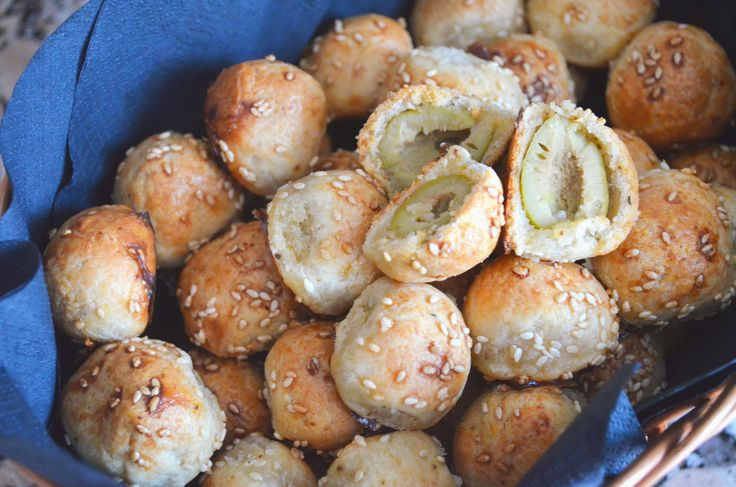 оливковые  колобки*** 40 больших оливок без косточек  150 г тёртого пармезана  120 г холодного масла, порезанного на кубики 200 г муки соль, кайенский перец 1 взбитое яйцо  1 столовая ложка семян кунжута