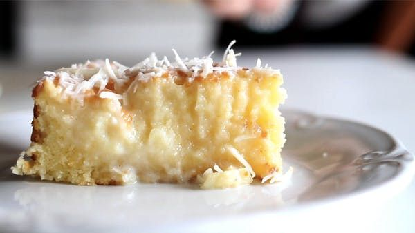Recipe with video instructions: A cake with a rich coconut base and grated coconut topping. Ingredients: 4 eggs, 1 1/2 cup sugar, 3 1/2 ounce butter, at room temperature, 26 tablespoons coconut milk, divided, 1 1/2 cup flour, 1 cup whole milk, divided, 1 tablespoon baking powder, 1 3/4 cup sweetened condensed milk, 3/4 cup grated coconut, for garnish