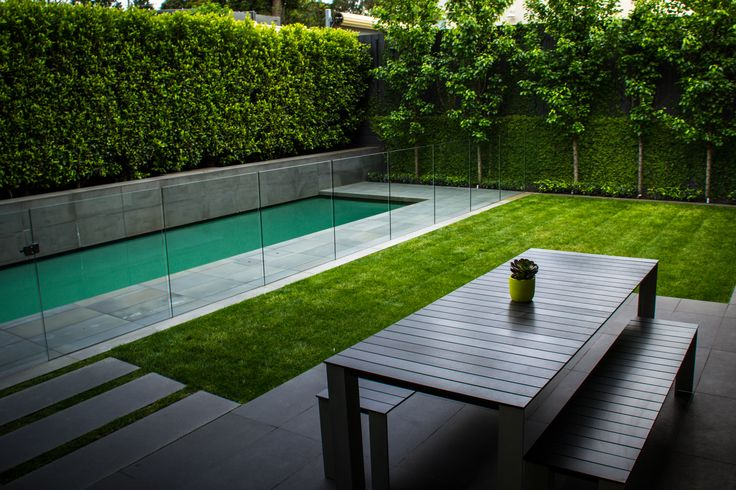 glass fence, stepping pavers and also trees