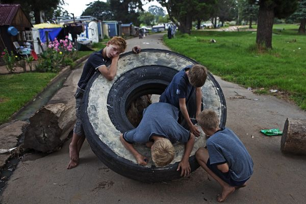 Children play on a tire being used to block the entrance to a squatter camp for poor white South Africans at Coronation Park in Krugersdorp.