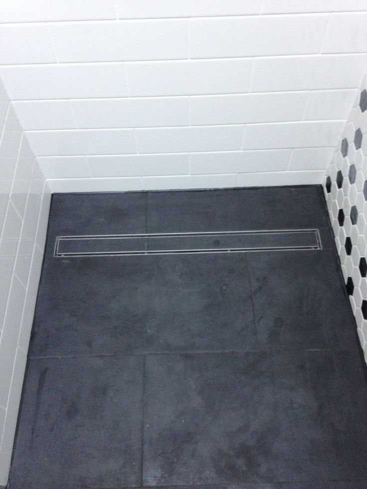 Floor tiles installed and grouted. New shower grate shown.