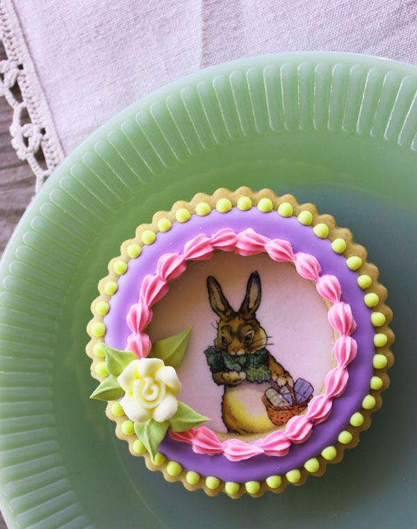 "Really cool idea..The bottom cookie is decorated using the wafer papering technique and pre-printed bunny wafer paper; then a window frame, aka a cookie ring with icing trim, is ""glued"" on top with thick Royal Icing."