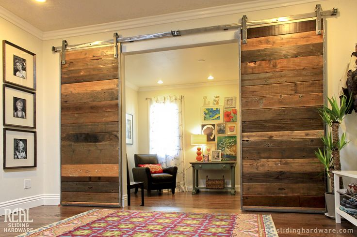 Mahogany exterior barn door by Real Carriage Door Co. with stainless steel box rail sliding hardware.