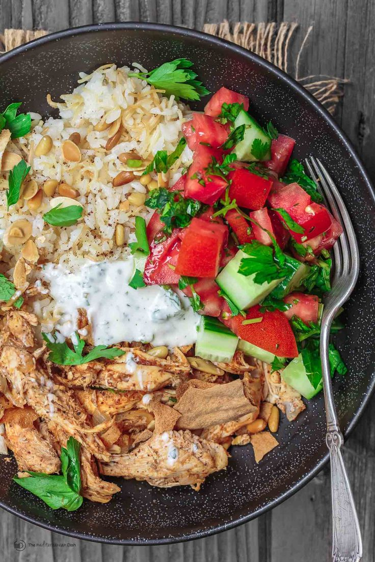 Lebanese chicken fatteh. Spiced poached chicken with toasted pita and mint yogurt sauce, served in dinner bowls with Lebanese rice and Mediterranean salad!
