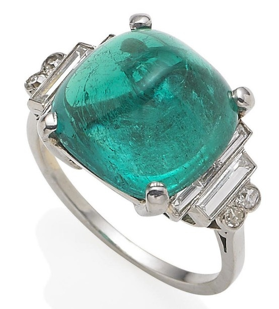 An emerald and diamond ring. The sugarloaf cabochon emerald weighing approximately 7.50 carats, between stepped baguette-cut diamond shoulders, with twin old brilliant-cut diamond collet accents, diamonds approximately 0.60 carat