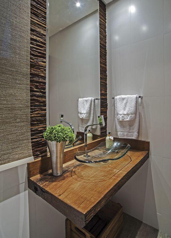 No lavabo, o estilo rústico fica evidente na bancada da pia, em madeira de demolição, valorizada pela leveza da cuba Canoa, em vidro incolor. Nas laterais do espelho, revestimento em ripas de madeira de demolição completa a proposta.