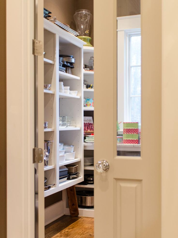 """The pantry doesn't always need to be hidden,"" says McGilvray. This one makes a statement with set of elegant French doors. The glass panel doors allow natural light to flow from the pantry's window into the kitchen and vice-versa. Antique-style glass knobs add to the charm."