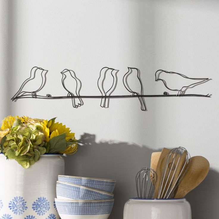 Add effortless style to your favourite aesthetic with this whimsical wall decor, crafted from metal and showcasing an understated silhouette. Its bird details bring natural charm to any space while its open design adds a breezy touch to any space. Play up this piece's traditional influence by adding it to a living room ensemble alongside a Chesterfield sofa and a pair of damask-pattern side chairs for a cohesive look, then accent the arrangement with an embroidered patchwork pillow for a…
