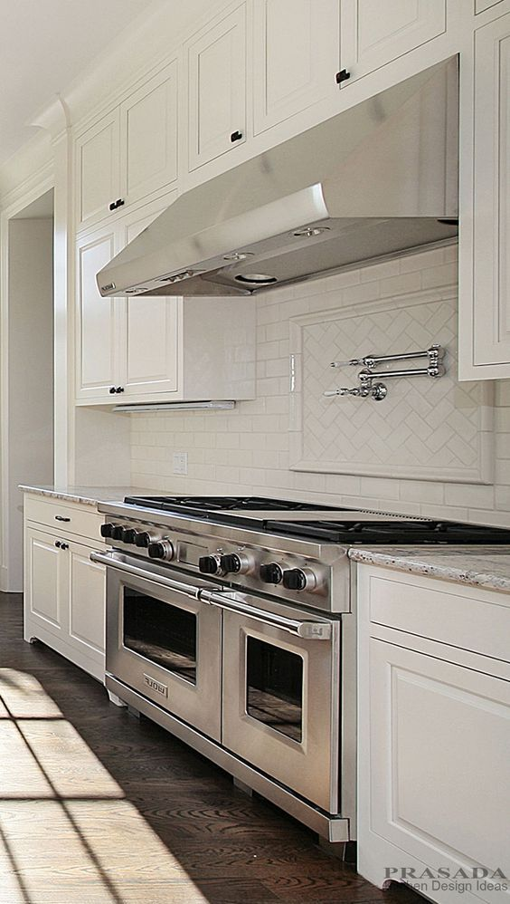 Transitional Kitchen. White Cabinetry With Large Stainless Hood And 48