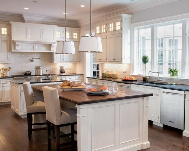 Another amazing kitchen! Love the white pendant lighting with silver chrome trim, white kitchen cabinets, black granite and butcher block countertops counter tops in this space! Love the upholstered parson stools chairs too!