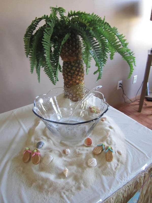 LUAU. Awesome punch bowl set up with sugar for sand, real shells, and pineapples for a palm tree still evoking the tropical concept of pineapples and hospitality.