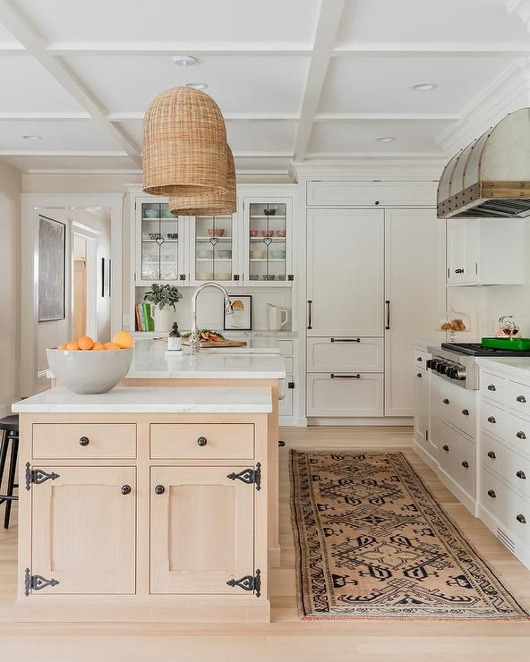 Blond wood floors frame a blond wood island boasting a farmhouse sink paired with a polished nickel gooseneck faucet.