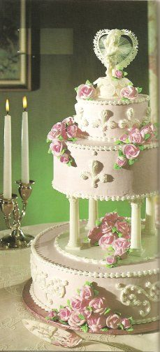 This cake has two layers elevated above the bottom, giving a center space for decorating with flowers. Perhaps you would like to substitute fresh pink roses instead of the icing ones featured?  Pink and Green Wedding Cake