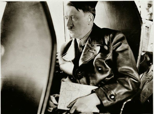 Hitler deep in concentration as prepared one of his rally speeches that captivated an entire brainwashed Germany for so many Nazi flag waving years of inhumane years of tears ( here he is on board ( looking bored ) his private plane that was escorted by Nazi fighter aircraft, to ensure his safe arrival ( thank goodness he arrived safely = his inept invasion of Russia ( despite reading about similar army blunders ) won us the war ( he was our best weapon in keeping his crack army at bay !! )