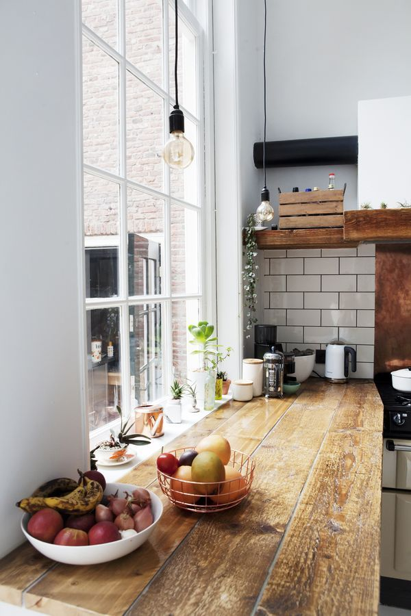 Industrial kitchen with wood countertops, white tile backsplash, and wire pendant lights