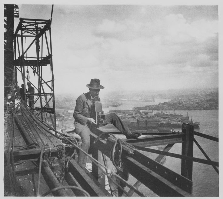 Perched on a girder, with his attention fixed on his box camera and one leg casually propped, Henri Mallard